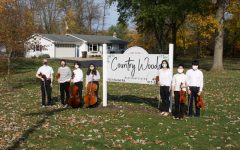 Student musicians in front of nursing home country woods sign