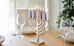 Blue and white menorah with all candles lit in the center of a table