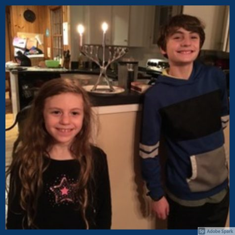 A photo of Raphael Gold standing to the right of the frame in a blue sweatshirt next to a menorah with 2 candles lit and Dalia Fermaglich standing next to him on his left