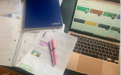 Notes and books on a desk next to a laptop with 2 highlighters