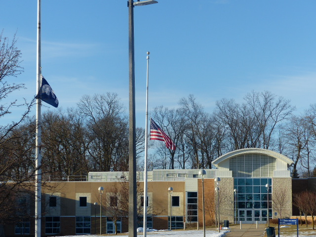East Lansing High School. Two flags are in front-The American flag, and the high school flag.
