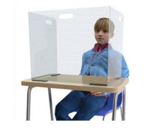 A boy sits a desk with a clear desk partion.