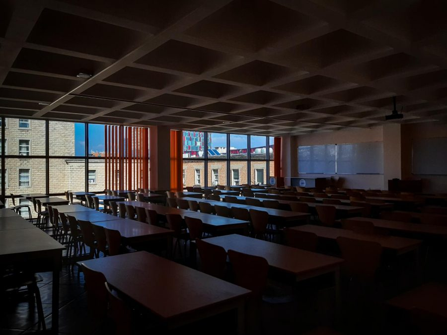 A dark epty classroom with desks in lines and a window at the edge of the classroom