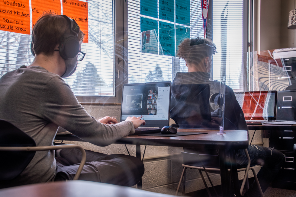 Fletcher Wasnich (9) and Allen McGrew (9) sitting on their desk wearing headphones with Google Meet on their laptop screen. Posters of french vocabularies are hanged on the window.