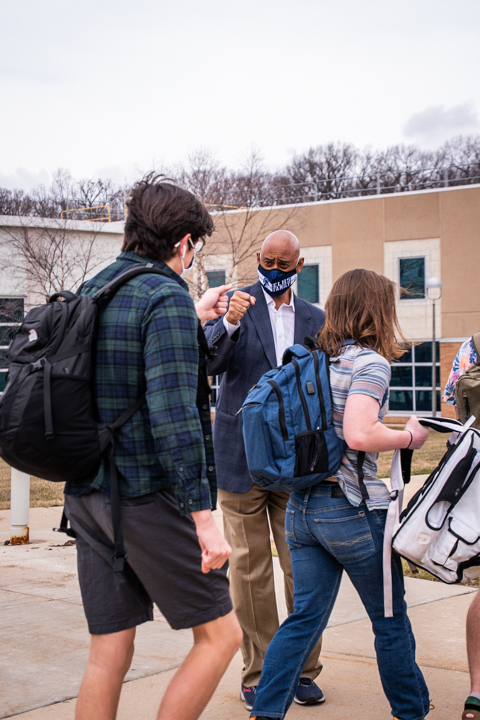 Wells gives air fist-bump to a student.
