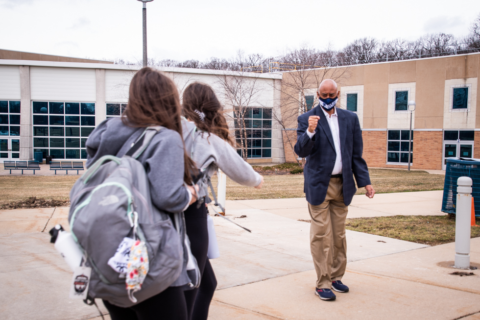 Principal Andrew Wells gives two students an air fist-bump.