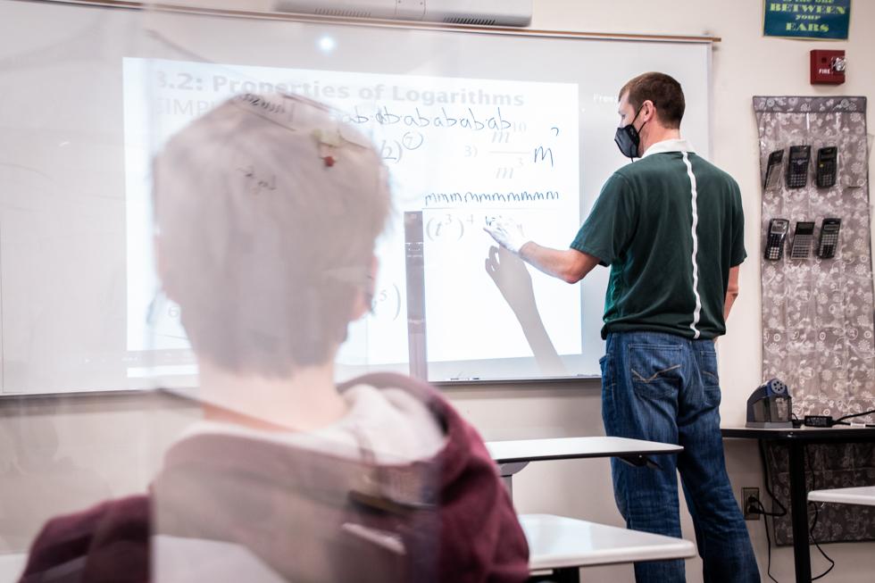 Math teacher Jeff Burgess writing on the board.