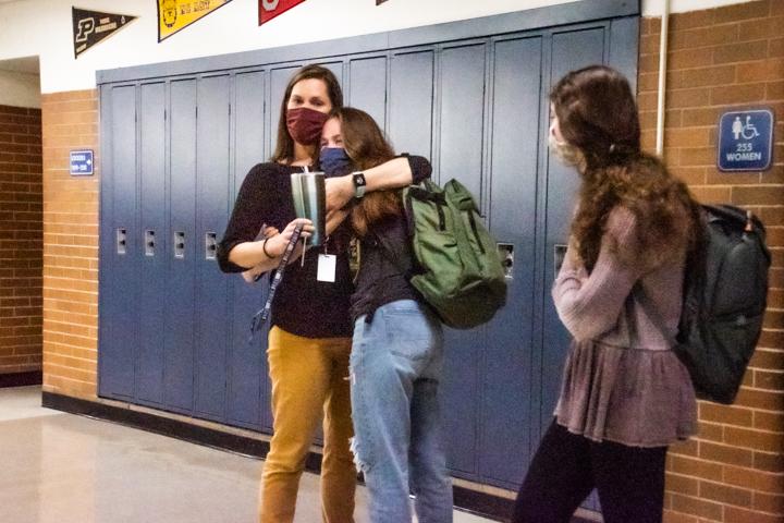Math teacher Maggie Moore hugs her daughter, Ginger Johnston (9). Sarah Bergdolt (9) stands beside them.