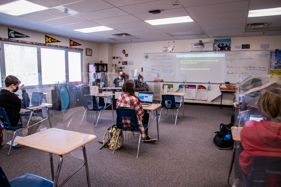 Classroom setup with students placed apart from each other. On each desk, plexiglas are placed in front the students. Teacher Ross Gorman teaching from his desk with a presentation on the board.