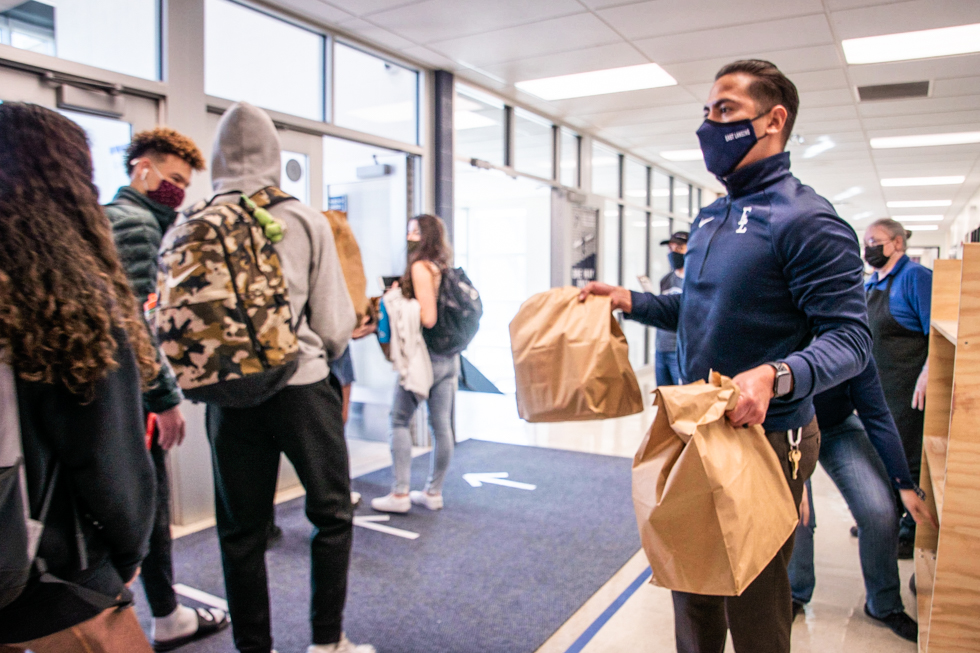 Morales handing out two weekend lunches to students as they exit the building