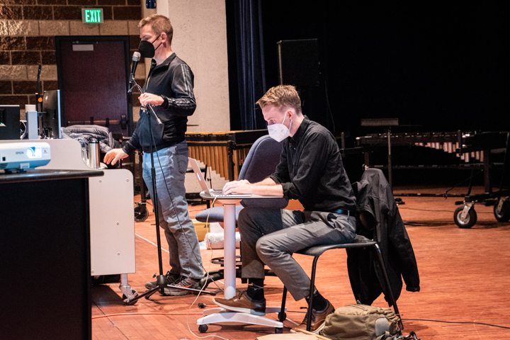 Band teacher David Larzelere talks with a mic on the stage. Beside him, band intern Cameron Halls typing on his laptop.