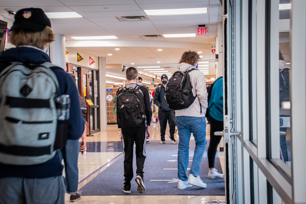 Students exiting the building through the main entrance.
