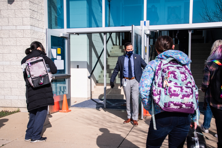 Associate Principal Matthew Morales directs student to which of the two doors they should enter through.