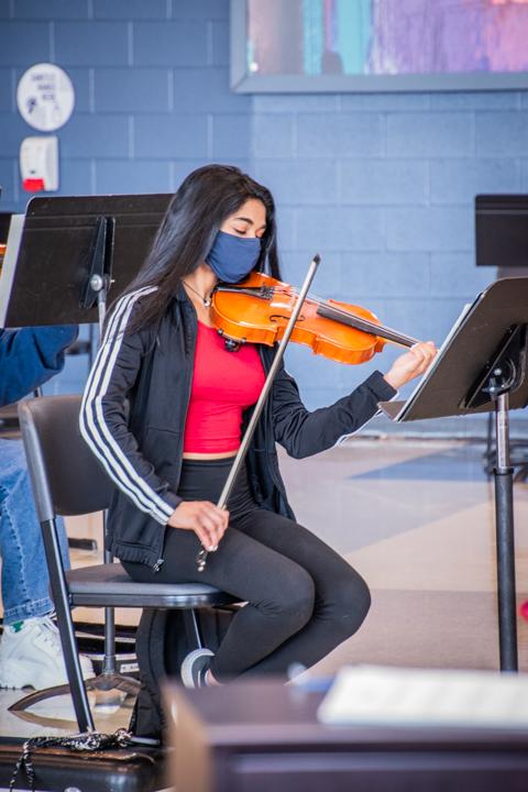 Iniya Umachandran (11) plays her violin with a mask on.
