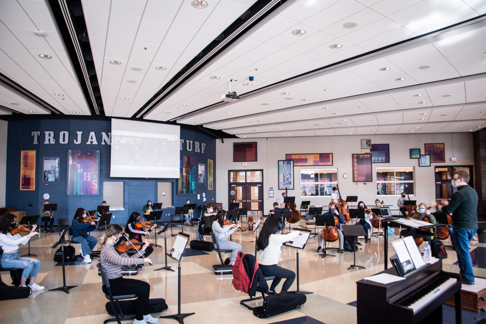 Orchestra class in the student union. Online students on Google Meet are displayed on the screen that is placed on the back wall of the student union.