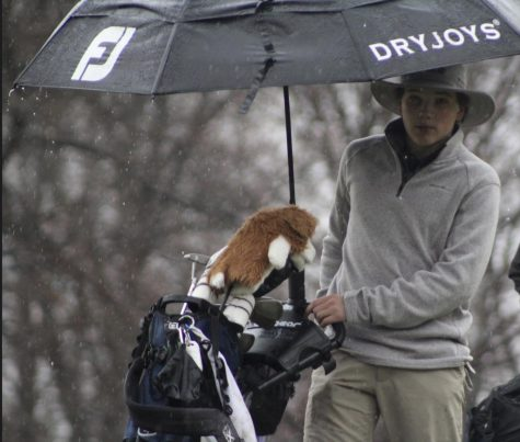 Golfer stands near his bag as he participates in a tournament