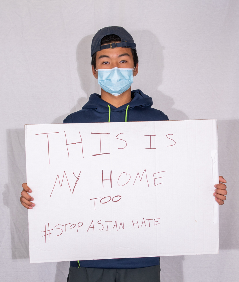 """Nick Chenault holds a sign which said: """"This is my home too #StopAsianHate."""""""