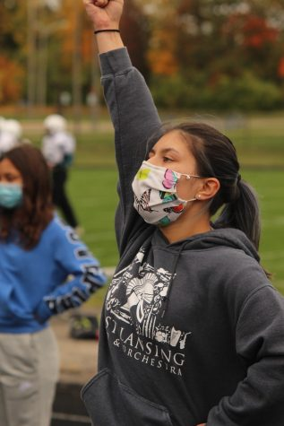 Grace Thompson chanting during cheer practice with a mask on.
