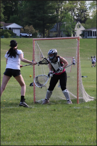 a girl holding a lacrosse stick runs up to a goal with another girl acting as goalie.