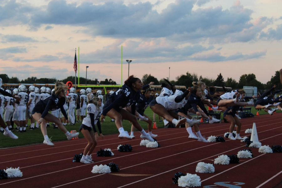 The+East+Lansing+varsity+cheer+on+Sept.+24+at+an+away+game+in+DeWitt%2C+cheer+will+accompany+the+football+team+as+well+as+engage+with+the+visiting+student+section.