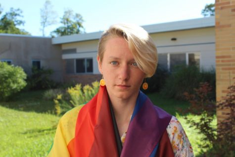 Keaton Kribs with a pride flag around their shoulders
