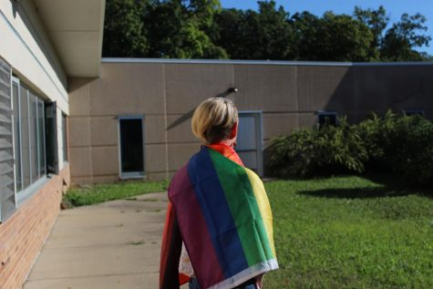 Keaton Kribs (10) stands with a pride flag on Sept. 24 outside of the 600 hallway.